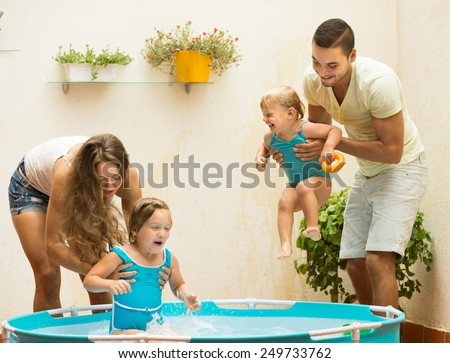 Joyful smiling young family of four playing in pool at terrace  - stock photo