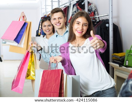 Joyful smiling young friends holding bags with purchases in apparel shop  - stock photo