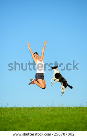Joyful sporty woman and dog jumping and having fun after running and exercising outdoor together. Female athlete and her pet celebrating sport success and freedom. - stock photo