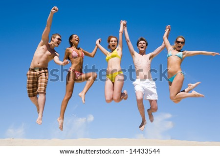 Joyful team of friends holding for hands each other and jumping - stock photo