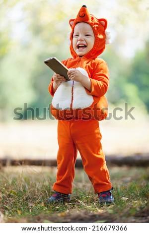 Joyful toddler boy in fox costume holding smartphone - stock photo