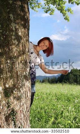 Joyful woman behind the tree trunk - stock photo