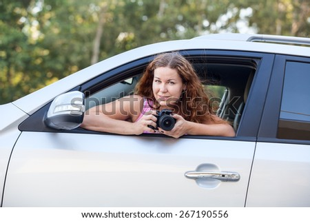 Joyful woman in pink shirt with camera in hand sitting in car - stock photo