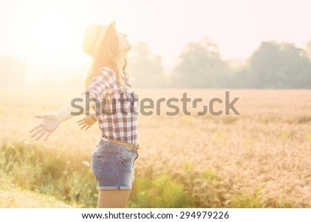 Joyful woman in the countryside with wheat field on background. She is wearing short jeans, a checked shirt and a straw hat. Freedom and happiness concepts. - stock photo