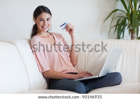 Joyful woman shopping online in her living room - stock photo
