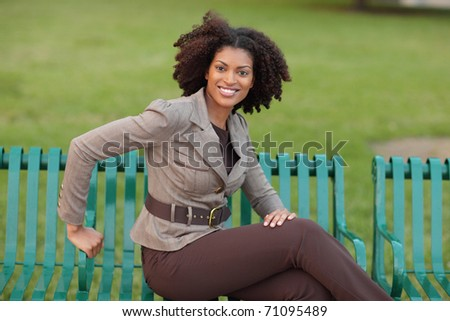 Joyful woman sitting in the park - stock photo
