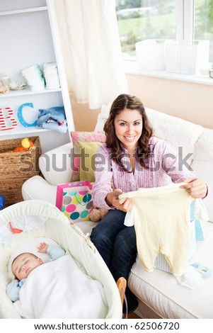Joyful woman sitting on the sofa with bags reading a card while her baby is sleeping in his cradle - stock photo