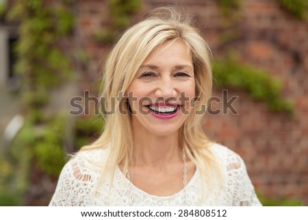 Joyful woman with shoulder length blond hair looking at the camera with a happy beaming smile, outdoors with a brick wall and creeper backdrop - stock photo