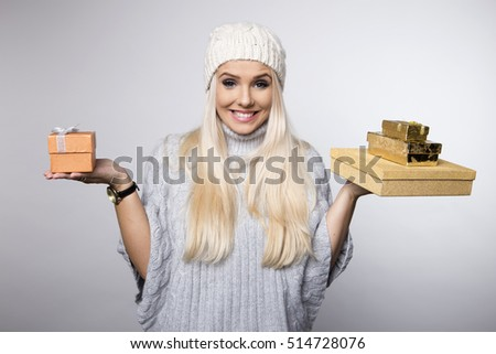 Joyful woman woman holding boxes with gifts on a grey background.