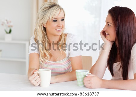 Joyful Women sitting at a table with cups in a kitchen - stock photo
