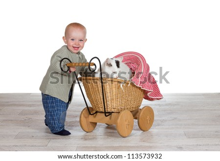 Joyful young baby standing holding the handle of a toy wicker pram with the family cat contentedly snuggled up on a blanket inside - stock photo