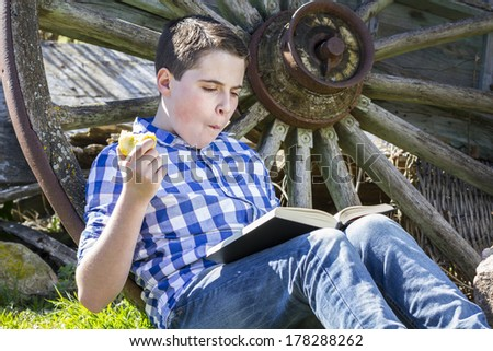 Joyful.Young boy reading a book in the woods eating an apple - stock photo