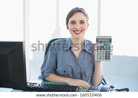 Joyful young businesswoman showing calculator sitting at her desk smiling at camera - stock photo