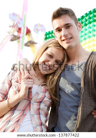 Joyful young couple holding each other while visiting an attractions park arcade with a ticket office and rides in the background. - stock photo