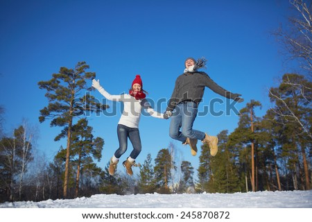 Joyful young couple jumping in winter park or forest - stock photo