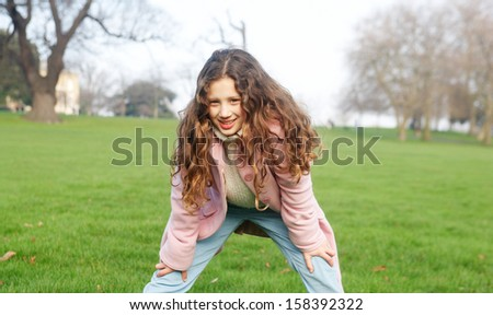 Joyful young girl child leaning on her knees while having a break from playing in a green grass park with leafless trees during a winter day outdoors. - stock photo