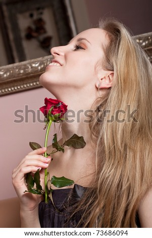 Joyful young lady with a red rose