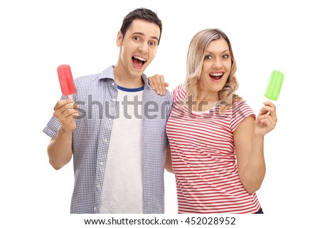 Joyful young man and woman holding popsicles and looking at the camera isolated on white background