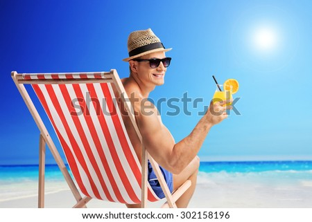 Joyful young man holding an orange cocktail seated in a sun lounger on a beach by the ocean - stock photo