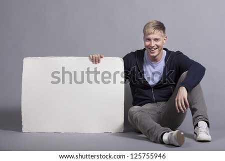 Joyful young man presenting white blank panel with space for text isolated on grey background. - stock photo