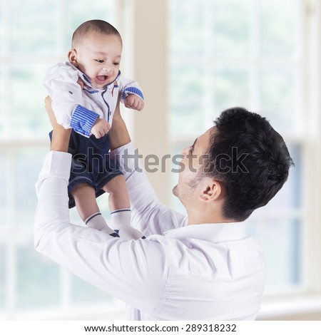 Joyful young man standing near the window at home while lifting up his baby