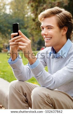 Joyful young man text messaging outdoors - stock photo