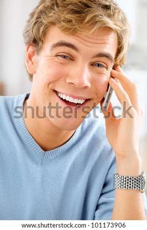 Joyful young man using mobile phone at home is happy and smiling