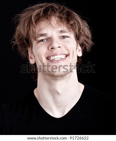 joyful young man with wild hair smiling - isolated on black background - stock photo