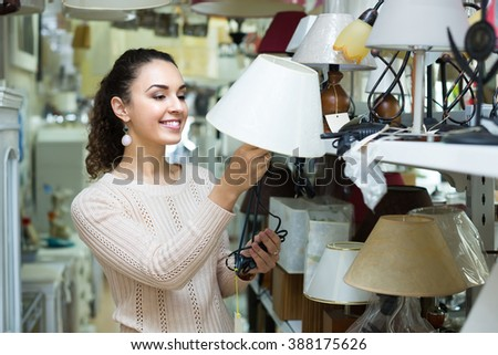Joyful young woman choosing decorative interior lights for home in mall