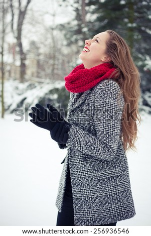 Joyful young woman outdoors on a snowy winter day - stock photo
