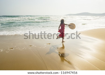 Joyful young woman running along the sunny beach - stock photo