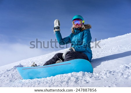 Joyful young woman snowboarder sitting on the snowy slope, strapped into snowboard at the ski resort - stock photo