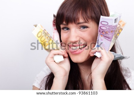 Joyful young woman with her hands full of Euros - stock photo