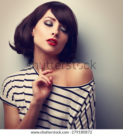 Joying young model touching skin with closed eyes in trendy blouse. Closeup vintage portrait - stock photo