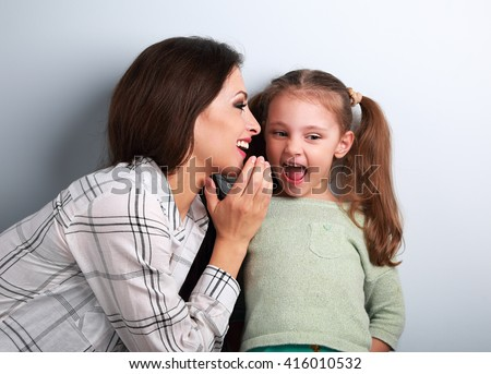 Joying young mother whispering the secret to her funny grimacing daughter in ear in studio.  - stock photo