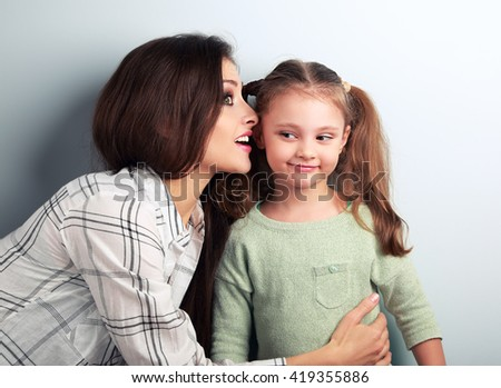 Joying young mother whispering the secret to her funny grimacing daughter in ear in studio - stock photo