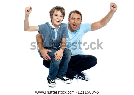 Joyous father and son cheering loud. Supporting their favorite teams. - stock photo