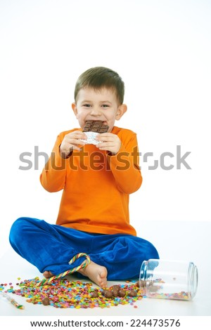 Joyous little kid eating chocolate sitting cross-legged on floor, sweets spilt. Isolated on white. - stock photo