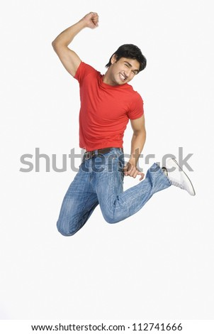 Joyous man jumping with raised arms - stock photo