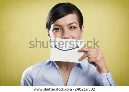 Joyous young businesswoman holding empty white card with space for text in front of her mouth, isolated on yellow background. - stock photo