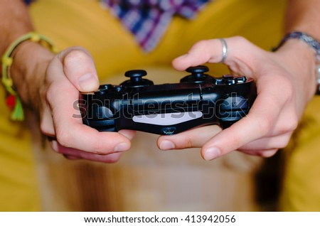 joystick in the hands of a young man who sits. Man dressed in a plaid shirt and yellow. boy pla video game - stock photo