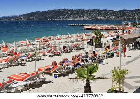 JUAN-LES-PINS, FRANCE - MAY 15: People sunbathing in sunloungers on the beach on May 15, 2015 in Juan-Les-Pins, France. Juan-Les-Pins is a well-known summer destination in the French Riviera