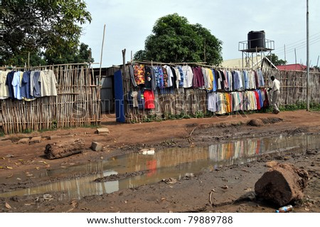 JUBA - JUNE 11: An unidentified man arranges shirts for sale at a clothing store on a downtown street in Juba, South Sudan, on June 11, 2011. South Sudan is one of the most undeveloped countries. - stock photo