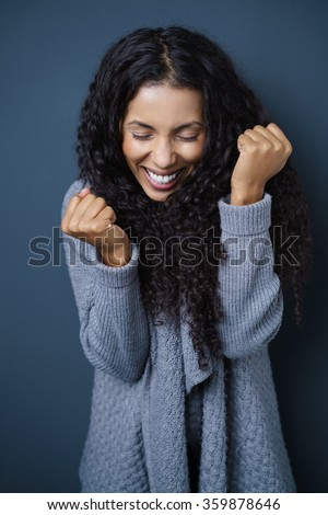 Jubilant vivacious young African American woman cheering in excitement as she clenches her fists, against a dark studio background - stock photo