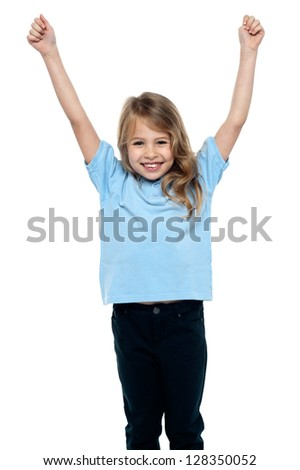 Jubilant young female kid celebrating success with her arms raised. - stock photo