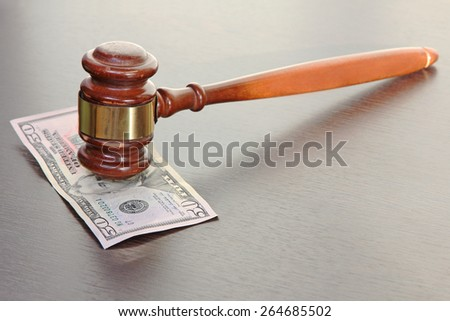 Judge gavel and fifty dollars banknote on wooden table. - stock photo