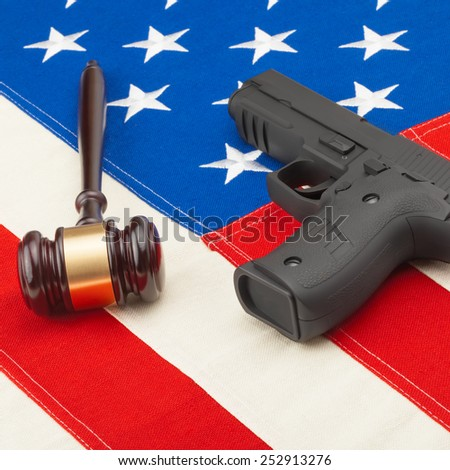 Judge gavel and hand gun over USA flag - studio shot - stock photo