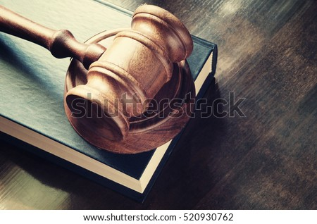 Judge gavel and legal book on wooden table close up