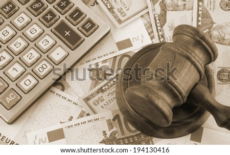 Judge gavel, calculator and euro and dollar banknotes - stock photo