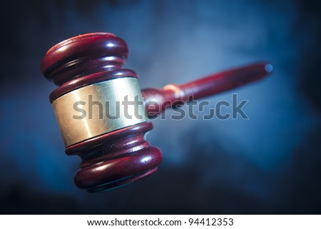 judge gavel on blue background with smoke and dramatic lighting - stock photo